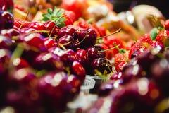 Körsbär och jordgubbar bär frukt i en marknad i barcelona Spanien royaltyfria foton