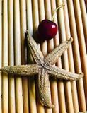 Körsbär och sjöstjärna på brun trämagasinkonst royaltyfri foto