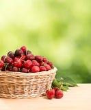 Körsbär på en trätabell arkivfoton