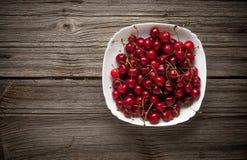 Körsbär på trätabellen med vattendroppar Arkivfoto