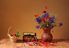 Körsbär, smycken och blommor i en vas Arkivbilder
