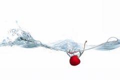 Körsbär som tappas in i vattenfärgstänk Arkivfoto