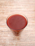 Körsbärsröd fruktsaft på den wood tabellen royaltyfri bild