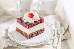 Körsbärsröd kaka för läcker gelé på den vita plattan med kräm fotografering för bildbyråer