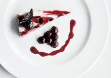 Körsbärsröd kaka på den vita plattan Royaltyfri Bild