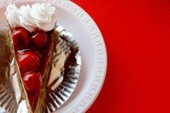 Körsbärsröd kaka på röd bakgrund Arkivfoto
