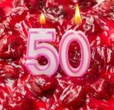 Körsbärsröd ostkaka med stearinljus för den 50th födelsedagen Fotografering för Bildbyråer