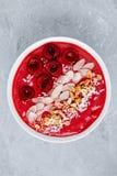 Körsbärsröd smoothiebunke med granola, mandlar, kokosnöten och nya bär royaltyfri fotografi