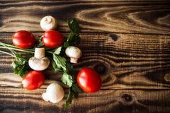 Körsbärsröd tomat och champinjoner på träbakgrund Arkivbilder