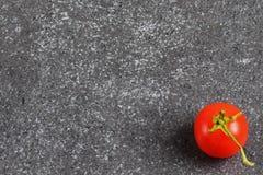 Körsbärsröd tomat på en grå abstrakt stenbakgrund Utrymme för text Arkivfoto