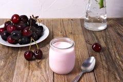 Körsbärsröd yoghurt i exponeringsglas, med nya körsbär arkivbild