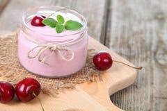 Körsbärsröd yoghurt och mogen körsbär royaltyfri bild