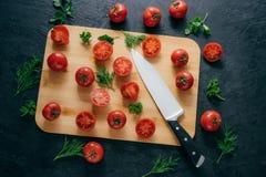 Körsbärsröda röda tomatskivor med kniven på skärbrädan för framställning av ketchup Organiska grönsaker för framställning smaklig royaltyfria bilder