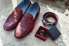 Körsbärsröda skor, bälte och vigselringar för man` s i en ask ansa tillbehör för ` s på bröllopdagen Royaltyfri Foto