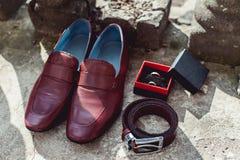 Körsbärsröda skor, bälte och vigselringar för man` s i en ask ansa tillbehör för ` s på bröllopdagen Fotografering för Bildbyråer