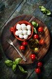 Körsbärsröda tomater, basilikasidor, mozzarellaost och olivolja f Arkivfoto