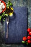 Körsbärsröda tomater, basilikasidor, mozzarellaost och olivolja f Royaltyfri Fotografi