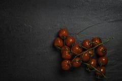 Körsbärsröda tomater för organisk mogen mini- Roma vinranka på en mörkerstenbakgrund arkivbilder