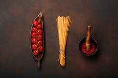 Körsbärsröda tomater fattar på ett trädiagram platta med pastamortel och röd peppar på rostig brun bakgrund royaltyfri foto