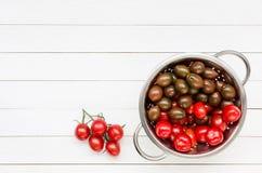 Körsbärsröda tomater i durkslag på den vita trätabellen Top beskådar Arkivbilder