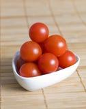 Körsbärsröda tomater i en bunke Arkivfoton