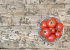 Körsbärsröda tomater i en bunke av exponeringsglas på en lantlig tabell Royaltyfri Foto
