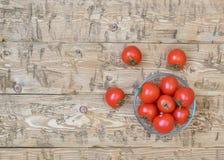 Körsbärsröda tomater i en bunke av exponeringsglas på en lantlig tabell Royaltyfria Bilder