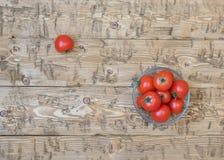 Körsbärsröda tomater i en bunke av exponeringsglas på en lantlig tabell Arkivbilder