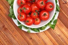 Körsbärsröda tomater i en bunke som omges av grön machegrönsallat Arkivbild