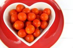 Körsbärsröda tomater i en formad hjärta bowlar på den röda plattan Arkivfoto