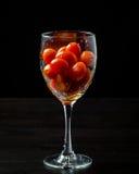 Körsbärsröda tomater i ett exponeringsglas på svart bakgrund Fotografering för Bildbyråer