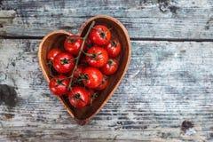 Körsbärsröda tomater i hjärtaformplatta på gammal träyttersida, spac Royaltyfri Fotografi