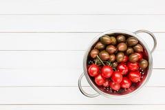 Körsbärsröda tomater i lantlig durkslag på den vita trätabellen Royaltyfri Fotografi