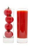 Körsbärsröda tomater inom av en exponeringsglas- och tomatfruktsaft Isolerat på Fotografering för Bildbyråer