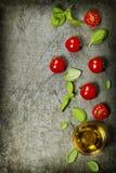 Körsbärsröda tomater med basilikasidor och olivolja arkivbild