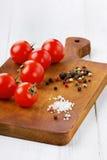 Körsbärsröda tomater med det salta färgpeppar och havet Royaltyfria Bilder