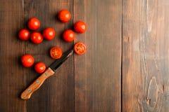 Körsbärsröda tomater med ett av dem som cuuting över den bruna trätabellen Royaltyfri Fotografi