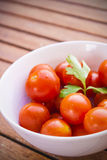 Körsbärsröda tomater med persilja i en vit bunke Arkivbild
