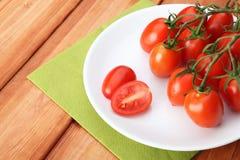 Körsbärsröda tomater och basilika på vit pläterar Royaltyfri Foto