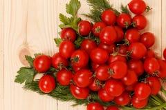 Körsbärsröda tomater och nya örter på träbakgrund Arkivfoton
