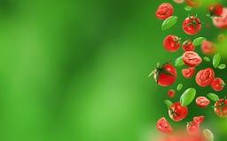 Körsbärsröda tomater och sidor som faller från luften arkivfoto