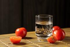 Körsbärsröda tomater och vodka på den matta hem- stilen arkivfoto