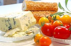 Körsbärsröda tomater, ost, rullar och vis mansidor arkivfoto