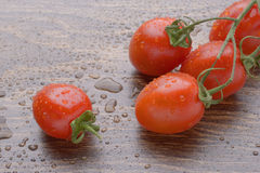 Körsbärsröda tomater på en mörk tabell En grupp i droppar av vatten Royaltyfria Foton