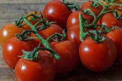 Körsbärsröda tomater på en trätabell med naturligt ljus royaltyfria foton