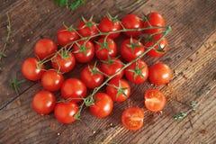 Körsbärsröda tomater på en träyttersida Arkivfoto