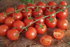 Körsbärsröda tomater på en träyttersida Arkivbild
