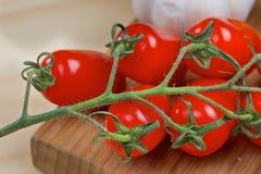 Körsbärsröda tomater på ett träbräde Royaltyfria Bilder