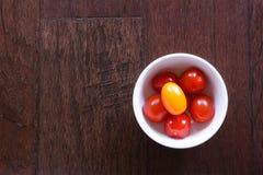 Körsbärsröda tomater på mörkt trä Fotografering för Bildbyråer