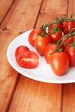 Körsbärsröda tomater på vit pläterar Royaltyfri Fotografi